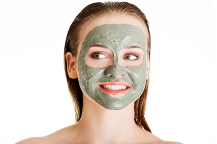 Beautiful woman with green clay facial mask